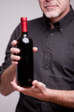 Bottle of red wine and hands of a man Stock Photos