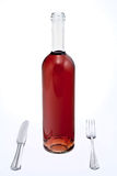 Bottle of red wine with knife and fork Royalty Free Stock Photography