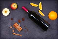 Bottle of red wine and mulled wine ingredients on black background. Spices and fruits for hot alcohol drink. Bottle of red wine and mulled wine ingredients on Royalty Free Stock Image