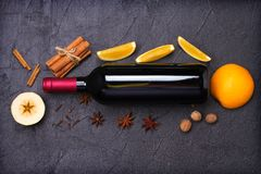 Bottle of red wine and mulled wine ingredients on black background. Spices and fruits for hot alcohol drink. Bottle of red wine and mulled wine ingredients on Stock Images