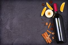 Bottle of red wine and mulled wine ingredients on black background. Spices and fruits for hot alcohol drink. Bottle of red wine and mulled wine ingredients on Stock Photo