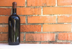 Bottle of red wine near wall of orange bricks. loft style Stock Image