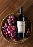 Bottle of red wine. The bottle of red wine on old wooden table Royalty Free Stock Photos