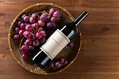 Bottle of red wine. The bottle of red wine on old wooden table Royalty Free Stock Photography