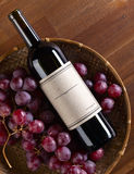 Bottle of red wine. The bottle of red wine on old wooden table Royalty Free Stock Images
