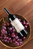 Bottle of red wine. The bottle of red wine on old wooden table Stock Images