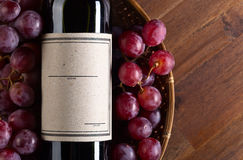 Bottle of red wine. The bottle of red wine on old wooden table Stock Image