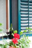 Bottle with red wine for perfect summer relaxed evening enjoyment. Glass and bottle with homemade red wine on window ledge in garden on a sunny day outside stock photography