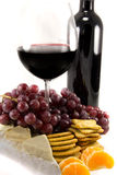 Bottle of red wine with some grapes. Picture of a bottle of red wine with grapes around, and crackers and clementins stock photos