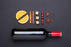 Bottle of red wine and spice for mulled wine on black background. Cinnamon, anise stars, orange, brown sugar. Bottle of red wine and spice for mulled wine on royalty free stock photo