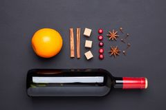 Bottle of red wine and spice for mulled wine on black background. Cinnamon, anise stars, orange, brown sugar. Bottle of red wine and spice for mulled wine on stock photography