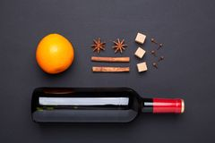 Bottle of red wine and spice for mulled wine on black background. Cinnamon, anise stars, orange, brown sugar. Top view royalty free stock photography