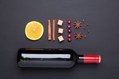 Bottle of red wine and spice for mulled wine on black background. Cinnamon, anise stars, orange, brown sugar. Bottle of red wine and spice for mulled wine on stock image