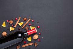 Bottle of red wine and spice for mulled wine on black background. Cinnamon, anise stars, orange, brown sugar. Bottle of red wine and spice for mulled wine on stock images