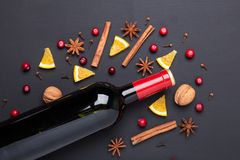 Bottle of red wine and spice for mulled wine on black background. Cinnamon, anise stars, orange, brown sugar. Bottle of red wine and spice for mulled wine on stock photos