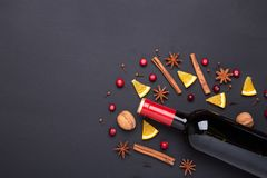Bottle of red wine and spice for mulled wine on black background. Cinnamon, anise stars, orange, brown sugar. Bottle of red wine and spice for mulled wine on royalty free stock images