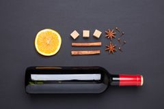Bottle of red wine and spice for mulled wine on black background. Cinnamon, anise stars, orange, brown sugar. Top view royalty free stock images