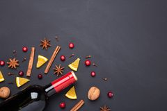Bottle of red wine and spice for mulled wine on black background. Cinnamon, anise stars, orange, brown sugar. Bottle of red wine and spice for mulled wine on royalty free stock photos