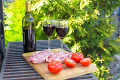 Bottle of red wine, steak and tomatoes on barbecue outdoors Stock Photos