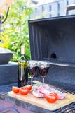 Bottle of red wine, steak and tomatoes on barbecue outdoors Royalty Free Stock Images