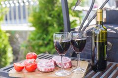 Bottle of red wine, steak and tomatoes on a picnic outdoors Royalty Free Stock Photography