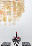 Bottle of red wine on a table, and decorative chandelier Royalty Free Stock Photos