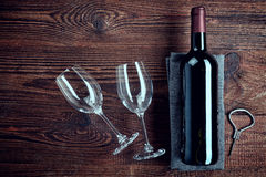 Bottle of red wine and two glasses. On wooden background from top view Royalty Free Stock Photos