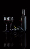 Bottle of red wine, two wine glasses and grapes on a black backg. Bottle of red wine,  wine glasses and grapes on a  black background Stock Photography