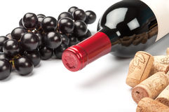 Bottle of red wine on white background. Bottle of red wine, grapes and corks on white background stock photos