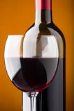 A bottle of red wine and a wine glass closeup Royalty Free Stock Photo