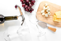 Bottle of red wine and wine glasses with cheese and grape aperitive on white background top view. Bottle of red wine and wine glasses with cheese and grape Stock Photo