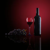 Bottle of red wine,  wine glasses and grapes Stock Image