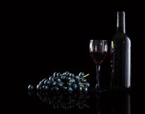 Bottle of red wine,  wine glasses and grapes. On a black backgroud Stock Photos