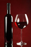Bottle of red wine and wineglass. Bottle and glass of red wine on red background Royalty Free Stock Photo