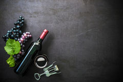 Bottle of red wine, wineglass and grapes. Bottle of red wine, wineglass, grapes and corks on dark background Stock Photo