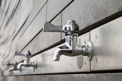 Bottle Refill Faucets. Shiny faucets on a monochromatic gray background Royalty Free Stock Image