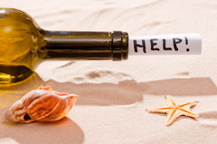 Bottle requesting assistance and seashells on  beach. Bottle requesting assistance and seashells on the beach Royalty Free Stock Photo