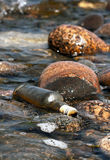 Bottle on rocks Stock Photography