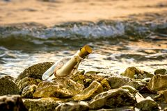 A bottle in rocky beach. Romantic letter in a bottle, a bottle in rocky beach, sunny beach, desperate help message, strange message, castaway on a deserted Stock Photo
