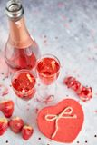 Bottle of rose champagne, glasses with fresh strawberries and heart shaped gift stock images