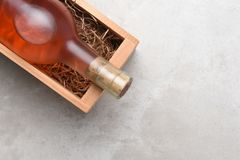 A bottle of Rose wine in a wood box. White Zinfandel, Blush Wine: A bottle of Rose wine in a wood box with packing straw. Item is positioned in the upper right Stock Photo