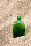 Bottle in sand. Empty green bottle sitting in sand on beach Stock Image