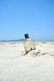 Bottle on a sand beach. Bottle buried a sand beach on a sunny beach Royalty Free Stock Photo