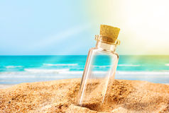 Bottle on sand beach with sun ray. Empty bottle on sand beach over blue sea and clear sky with sun ray Royalty Free Stock Photography