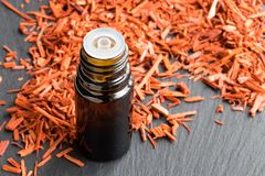 A bottle of sandalwood essential oil with sandalwood on a gray b. A bottle of sandalwood essential oil with sandalwood in the background Royalty Free Stock Images