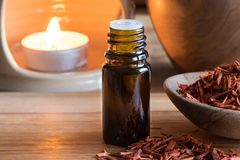 A bottle of sandalwood essential oil with sandalwood. And copy space, with an aroma lamp in the background Stock Photos