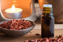 A bottle of sandalwood essential oil with sandalwood pieces. And an aroma lamp in the background Stock Photo