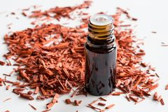 A bottle of sandalwood essential oil with sandalwood on white ba stock photos