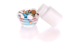 Bottle and saucer with many-colored pills. Transparent saucer and white bottle with many-colored pills Stock Images