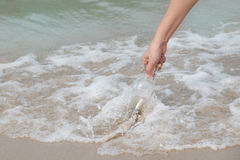 Bottle-sea. Hand holding a bottle with a letter inserted inside by the sea Royalty Free Stock Photography